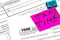 Imposez l'heure écrite sur un trombone lumineux de note d'autocollant pour un impôt Image libre de droits