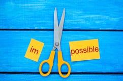 Imposible es el concepto posible la tarjeta con el texto imposible, tijeras cortó una palabra a ellos concepto del éxito y del de foto de archivo libre de regalías