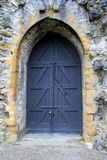 Imposing black doors in stone archway Stock Photo