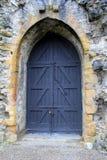 Imposing black doors in stone archway Stock Photo