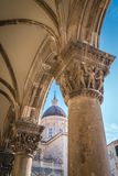 Imposing Church tower dome in Dubrovnik. Imposing Church tower dome and close up of the arched roof supporting columns with carved figures, Dubrovnik Old Town Stock Images