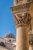 Imposing Church tower dome in Dubrovnik. Imposing Church tower dome and close up of the arched roof supporting columns with carved figures, Dubrovnik Old Town Stock Photos