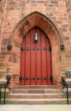 Imposing detail of old church doors. Imposing detail of red church doors with heavy black metal hardware and impressive brick archway at entrance Royalty Free Stock Images