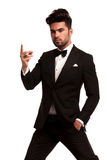 Imposing fashion man in tuxedo snapping his fingers. On white background Stock Photography
