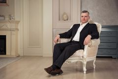 Imposing man is sitting in a white chair at the vintage interior. Studio shoot Stock Photo