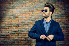 Imposing mature man. Portrait of a well-dressed imposing man in sunglasses. Fashion hair styling, barbershop. Brick wall background Stock Photography