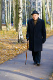 Imposing Old Man. Portrait of walking old man in a hat with walkingstick Royalty Free Stock Photos