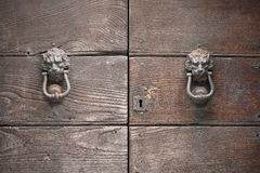 Imposing wooden door closed and barred with two symmetrical clappers ancient medieval style in the shape of lion Royalty Free Stock Images