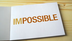 Impossible becomes possible by fading letters printed on the notebook page.