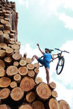 Impossible. Fit man with his bicycle climbing on top of large pile of logs stock images
