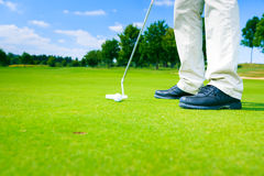 An Impossible Putting Challenge. Golf player getting ready to put, but the whole is way too small for the ball. concept for impossible challenges, problems, etc Stock Images