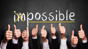 Impossible turns to possible. Many thumbs up to 'impossible' turns to 'possible Royalty Free Stock Photography