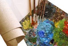 Imposti per la pittura - la tela di canapa, la gamma di colori, pennelli Fotografie Stock