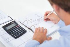 Imposto calculador do homem de negócios no escritório Fotografia de Stock
