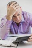 Imposto calculador preocupado do homem no fundo branco Imagens de Stock Royalty Free