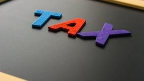 IMPOSTO do alfabeto na placa preta Fotografia de Stock