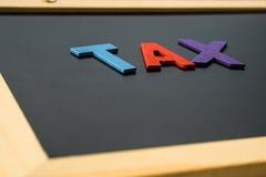 IMPOSTO do alfabeto na placa preta, conceito da finança Foto de Stock