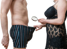 Impotence concept. Sexy woman is looking on her lovers penis with magnifier Stock Image