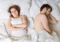 Impotensbegrepp Den unga mannen sover i säng Ledsen, besviken och unsatisfied flickvän arkivbild