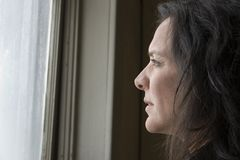 Impoverished Woman. Thirty-eight year old impoverished woman looking out window of low income home Royalty Free Stock Photography