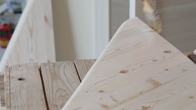 Impregnation of diagonally arranged wooden step with a brush. Construction and painting works from wood. Varnishing and gloss of wood in the shop. Close up stock footage
