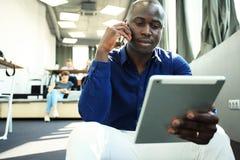 Imprenditore afroamericano felice che per mezzo del computer della compressa Fotografia Stock Libera da Diritti