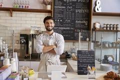 Imprenditore al contatore della caffetteria, armi attraversate immagini stock
