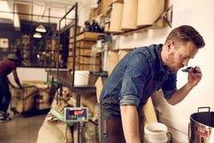 Imprenditore che controlla l'aroma del chicco di caffè di recente arrostito Fotografia Stock Libera da Diritti