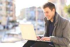 Imprenditore che lavora con un computer portatile all'aperto Fotografie Stock