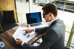 Imprenditore che lavora con un computer portatile e che tiene un documento in un ufficio Fotografia Stock Libera da Diritti
