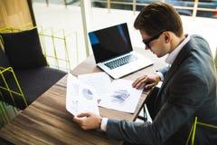 Imprenditore che lavora con un computer portatile e che tiene un documento in un ufficio Fotografie Stock