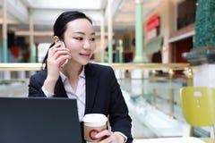 Imprenditore che lavora con un telefono e un computer portatile in una caffetteria Fotografia Stock Libera da Diritti