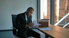 Imprenditore con la scatola commovente in ufficio che disimballa gli oggetti video d archivio