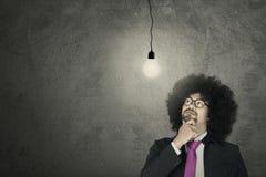 Imprenditore di afro che esamina lampadina Fotografia Stock Libera da Diritti