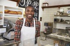 Imprenditore dietro il contatore ad una barra del panino fotografia stock libera da diritti