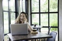 Imprenditore felice che lavora con un telefono e un computer portatile in un caffè s Fotografia Stock Libera da Diritti