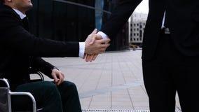 Imprenditore felice che stringe le mani con l'uomo d'affari invalido all'aperto video d archivio