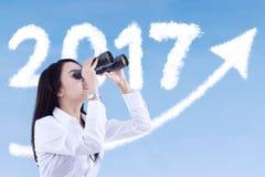 Imprenditore femminile che esamina nuvola con binoculare Fotografie Stock
