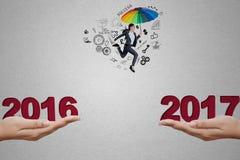 Imprenditore femminile che salta verso il numero 2017 Immagini Stock