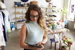 Imprenditore femminile che utilizza il computer della compressa nel negozio di vestiti fotografia stock