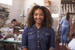 Imprenditore femminile della corsa mista nello studio di progettazione dell'abbigliamento immagine stock