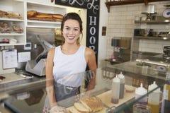 Imprenditore femminile dietro il contatore ad una barra del panino fotografie stock libere da diritti