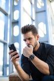 Imprenditore frustrato che ha problema, leggente via le risposte negative mobili circa il suo progetto fotografie stock