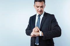 Imprenditore maschio occupato che controlla tempo sopra fondo Fotografia Stock