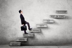 Imprenditore maschio sulle scale con il piano di strategia Immagine Stock