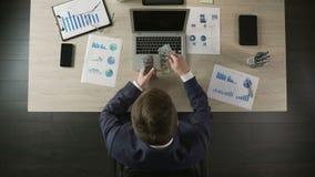 Imprenditore occupato che conta le banconote del dollaro americano, riuscito investimento, vista superiore video d archivio