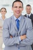 Imprenditore serio che posa con i suoi colleghi su fondo Fotografia Stock