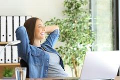 Imprenditore soddisfatto che guarda attraverso la finestra immagine stock