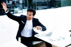 Imprenditore sorridente che ondeggia la sua mano che dice ciao a qualcuno, riuscito maschio felice Immagini Stock