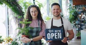 Imprenditori della donna e dell'uomo che tengono segno e pianta aperti nel negozio di fiore stock footage